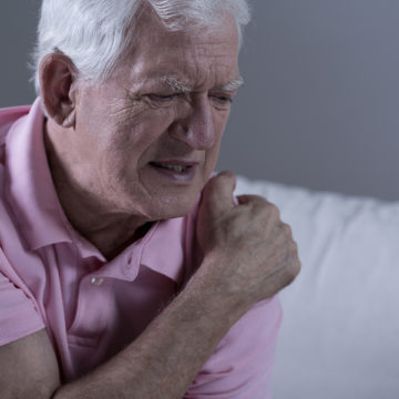Senior suffering from shoulder pain, horizontal view