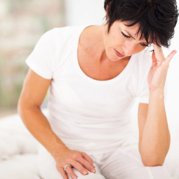 middle aged woman sitting on bed and having headache